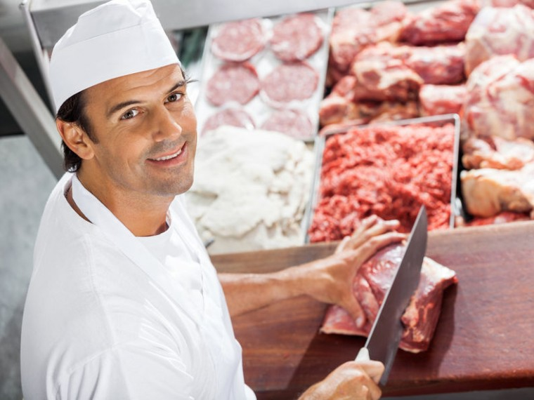 36433291 - confident butcher cutting meat at counter